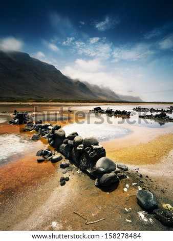 salt on a sunny day with high clouds with mountains in the background and rocks in the foreground row in Lanzarote (Spain) - stock photo