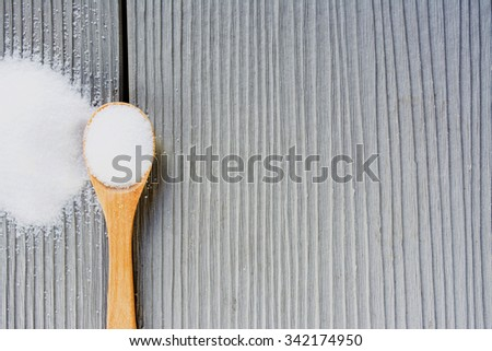 salt on a wooden scoop and salt sprinkled on a wooden  - stock photo