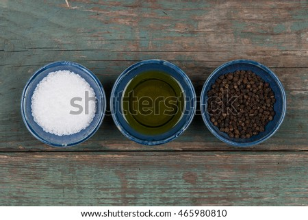 Salt, pepper and oil on a wooden table, stock picture