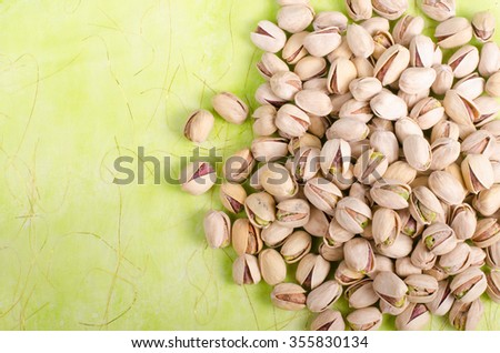 Salt pistachios on green background. Free space for your text. - stock photo