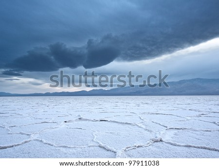 Salt polygons on the Badwater Salt Flats in Death Valley National Park as an ominous storm rolls in. - stock photo