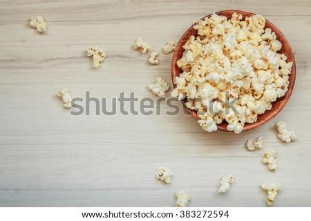 Salt popcorn on the wooden table - stock photo