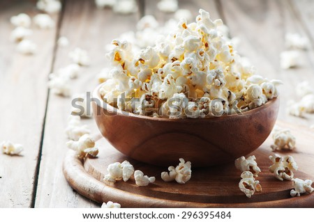 Salt popcorn on the wooden table, selective focus - stock photo