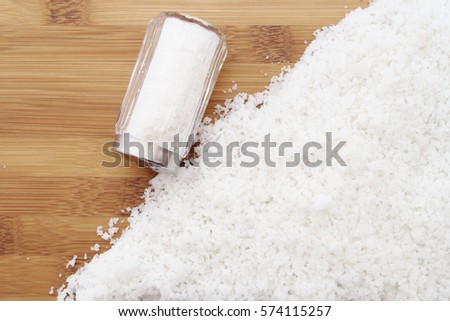 Salt shaker and heap of organic sea salt on wooden table