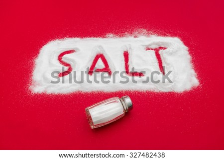 Salt shaker and text out of white powder on a red background suggesting toxic ingredients if used in an excessive manner - stock photo