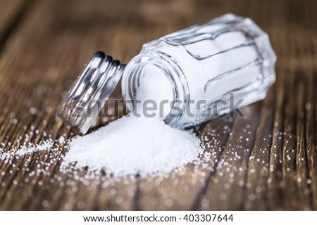 Salt Shaker (close-up shot; selective focus) on vintage wooden background - stock photo