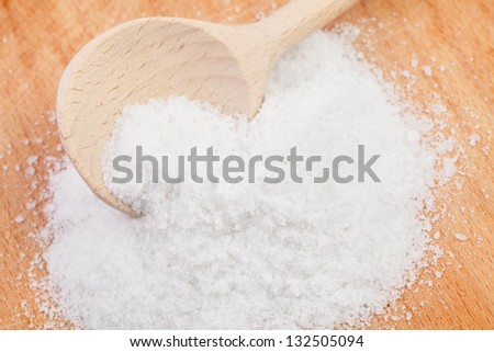 salt spoon on wooden desk closeup - stock photo