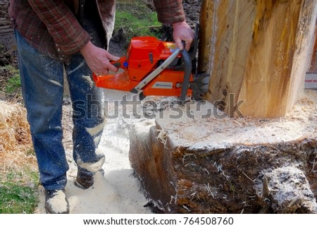Salt Spring Island, British Columbia, April 9, 2017: Sawdust piles up on a man's feet as he cuts a block of wood with a chainsaw.
