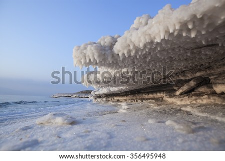 Salt Structures above an below with the sea in the background and a blue sky - stock photo