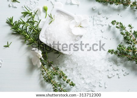 salt with flowers, rosemary and savory twigs on white wood table - stock photo