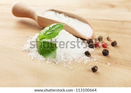 salt with fresh basil, garlic and pepper on wooden table - stock photo