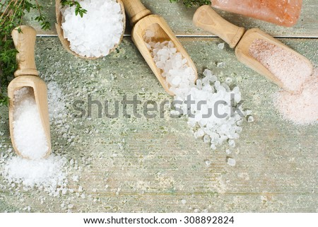 salt with savory on aged wooden table - stock photo