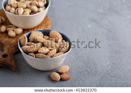 Salted almonds and pistachios in a shell on gray background - stock photo