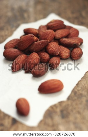 salted almonds on old wood background - stock photo