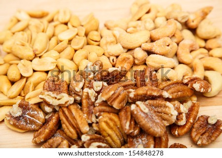 Salted and Roasted peanuts, cashews and pecans on a wood cutting board - stock photo