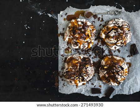 Salted caramel and chocolate meringues over dark grunge surface, top view, copy space. - stock photo