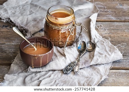 Salted caramel sauce in a rustic glass jar and brown ceramic cup on a wooden desk. Black background - stock photo