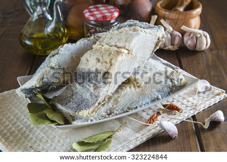 Salted cod cut with ingredients and utensils on the table of the kitchen for cooking - stock photo