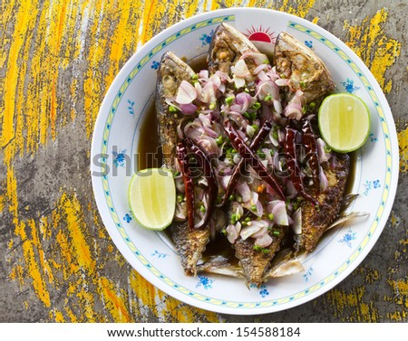 Salted fish fried in a white plate on the table of the ancient yellow. - stock photo