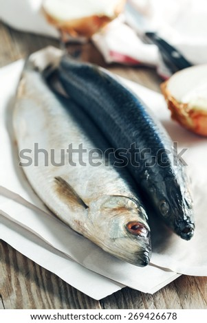 Salted herring on a wooden table - stock photo