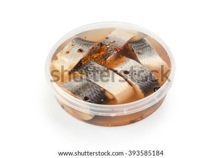Salted herrings in a plastic pot isolated on the white background