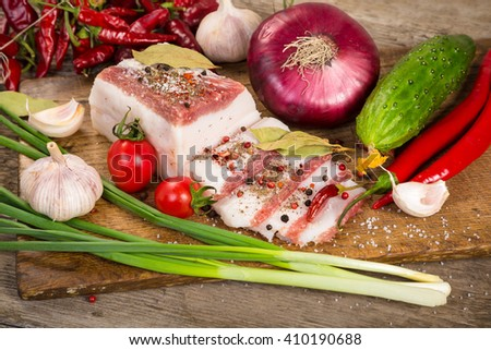 salted lard with spices and vegetables on wooden cutting board
