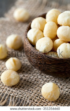 salted macadamia nuts on wooden surface - stock photo