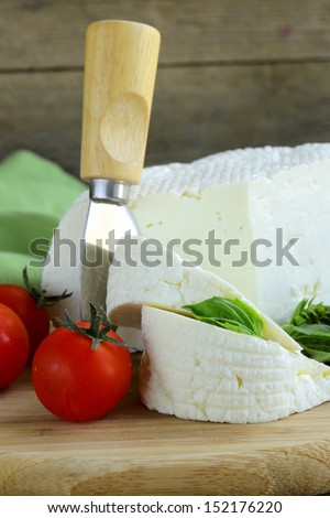 salted milk cheese (feta cheese) on a wooden chopping board