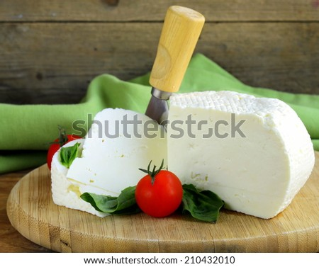 salted milk cheese (feta cheese) on wooden plate