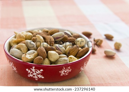 Salted mix nuts on colourful table cloth - stock photo