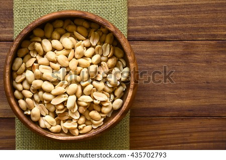 Salted peanuts in wooden bowl, photographed overhead on dark wood with natural light (Selective Focus, Focus on the top peanuts)