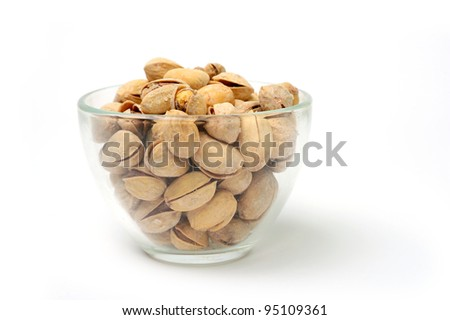 Salted pistachio in a transparent bowl on white background - stock photo