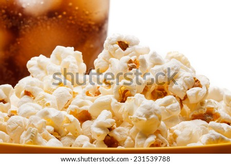 Salted popcorn grains in the dish and a glass of cola on the white background - stock photo