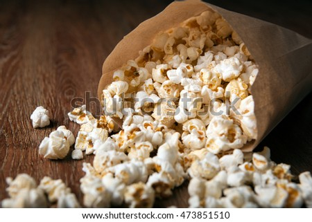 salted popcorn in a paper bag on a wooden table close up