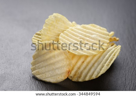 salted potato ships on old slate board, selective focus - stock photo