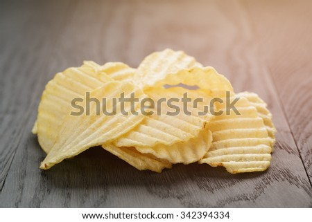 salted potato ships on old wooden table, vintage toned - stock photo