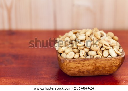 Salted, roasted, peanuts in a wooden bow, on white background - stock photo