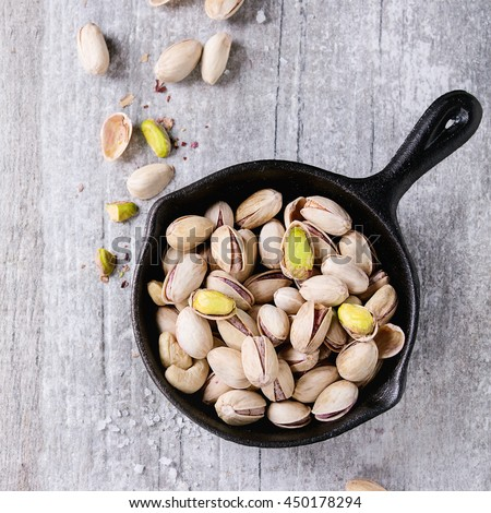 Salted roasted pistachios nuts with shell and salt  in black small cast-iron pan over white wooden textured background. Top view. Square image - stock photo