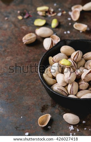 Salted roasted pistachios nuts with shell and salt  in  in black small cast-iron pan over old rusty iron textured background. With copy space - stock photo
