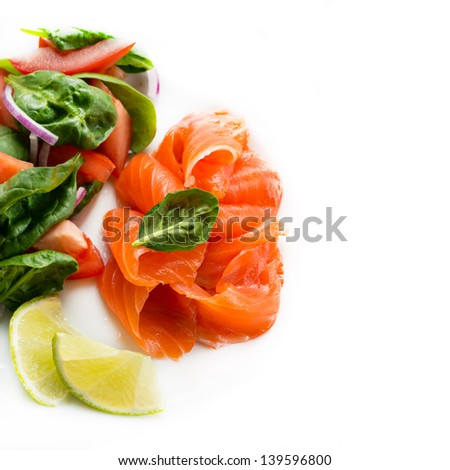 Salted salmon with fresh green salad and lime on white background, copy space, selective focus