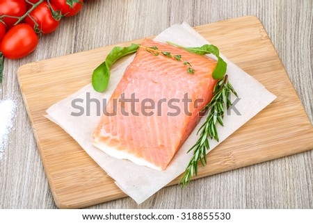 Salted salmon with rosemary and thyme on the wood background - stock photo