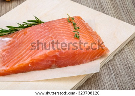 Salted salmon with rosemary and thyme on the wood background
