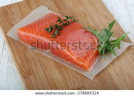 Salted salmon with thyme leaves on the wood background - stock photo