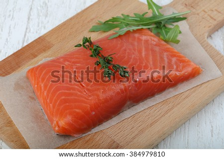 Salted salmon with thyme leaves on the wood background