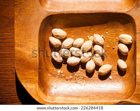 Salted snacks. Closeup of pistachios nuts in brown wooden bowl. Unhealthy food. - stock photo