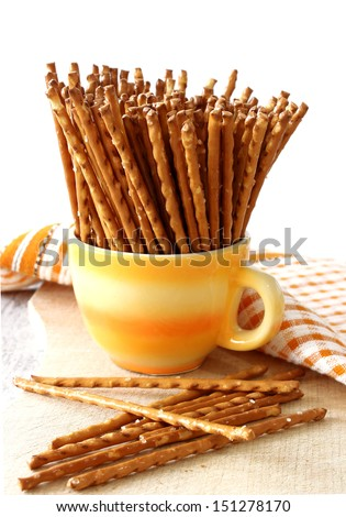 salted sticks in yellow cup on wooden