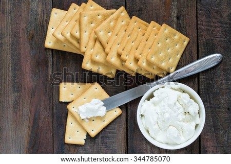 Saltine crackers on a wooden table and ricotta in a jar, topped with knife on cracker - stock photo