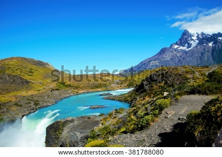 SALTO GRANDE, TORRES DEL PAINE NATIONAL PARK, CHILE - FEBRUARY, 5, 2016: Waterfall between green and brown hills, in the background snow covered mountain