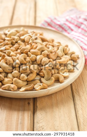 Salty cashew nuts in wooden plate over pallet background - stock photo