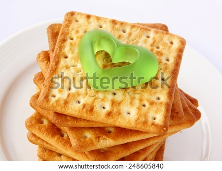 Salty Crackers with green heart are on white background. - stock photo